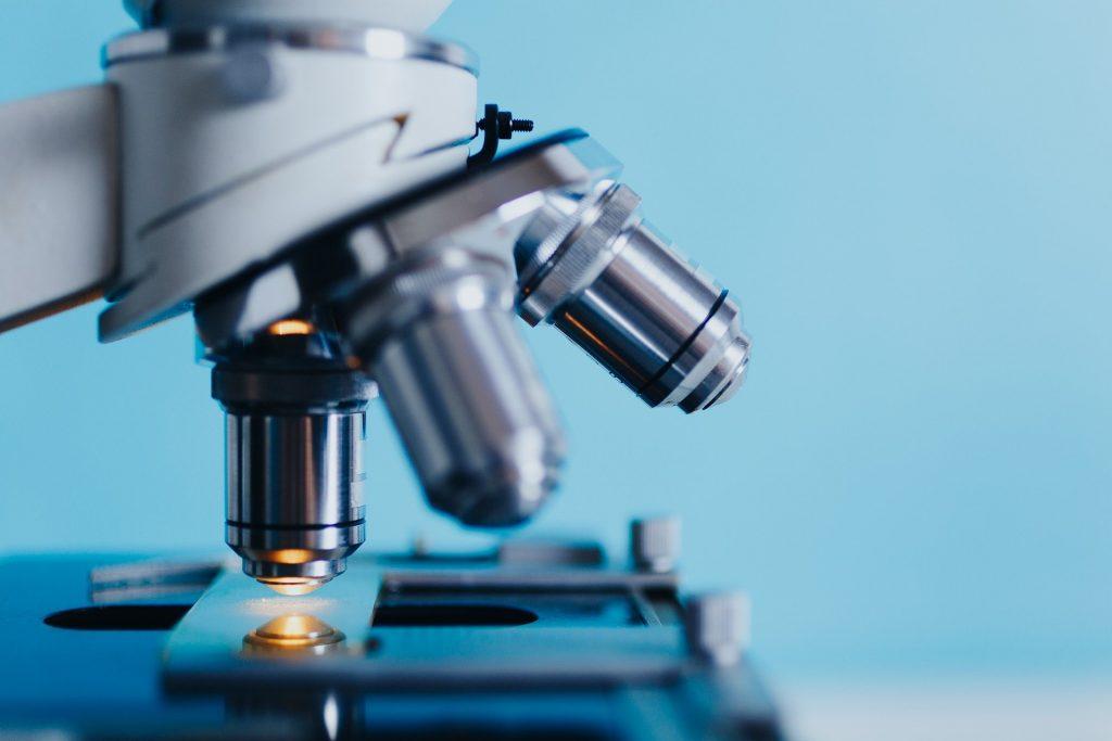 Detalle de un microscopio con fondo azul y una luz amarilla en el objetivo.