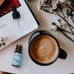 bote de pura calma sobre una mesa en la que hay una taza de café, una revista y unas flores silvestres