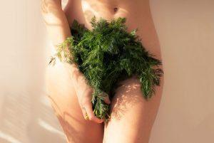 Un cuerpo femenino que sostiene vegetales en su vientre para ilustrar el post de cbd y menstruación