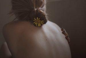 chica de espaldas con una flor en el moño para ilustrar el uso tópico del cbd