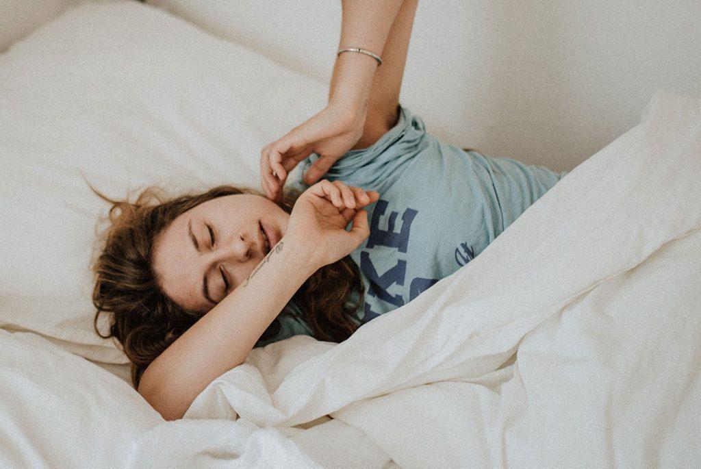 mujer en la cama tocandose la mandíbula para ilustrar bruxismo y cbd