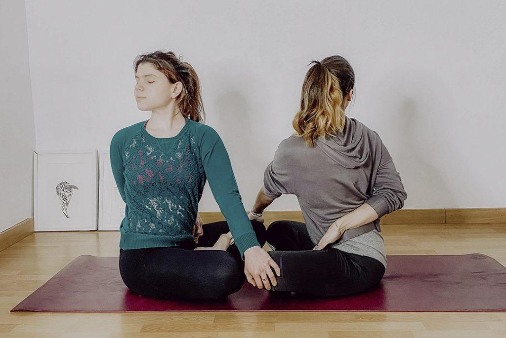 Ainara y Fede sobre una esterilla haciendo una postura de yoga para ilustrar por qué deberías hacer yoga en casa
