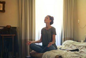 mujer meditando sobre la cama