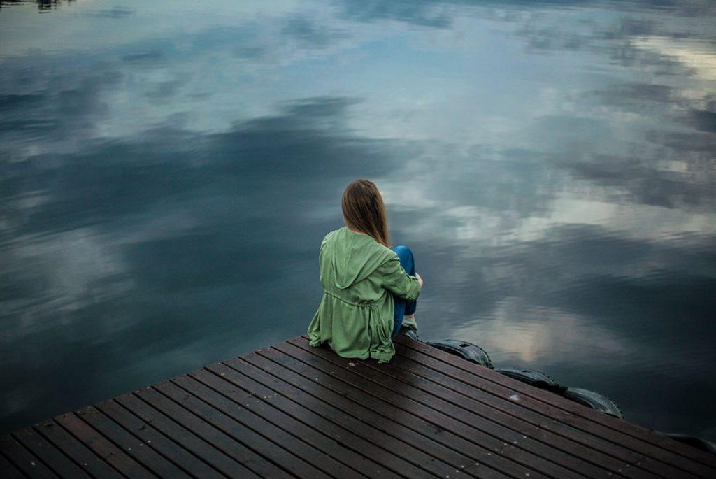 mujer sola al borde del agua para ilustrar el post de estrés post traumático y cbd